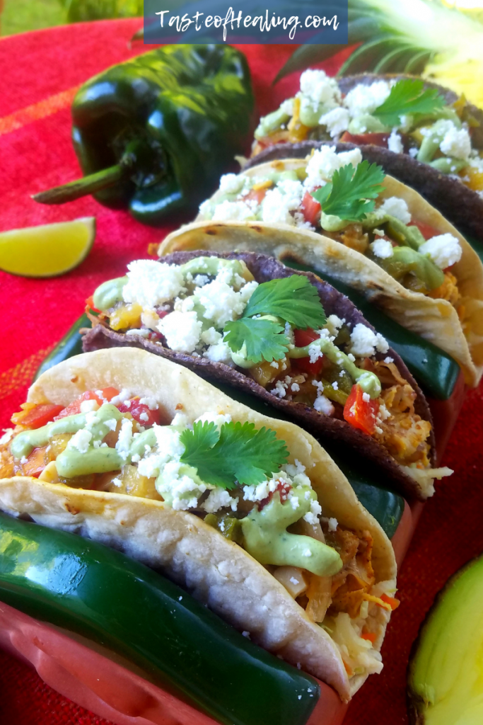 A plate of Grilled Pineapple Poblano Chicken Tacos with Avocado Cilantro Crema