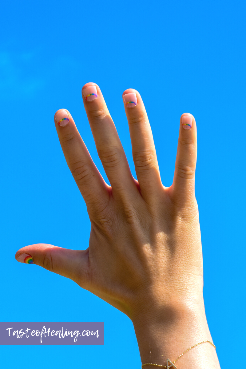 Hand raised in the air with blue sky behind it